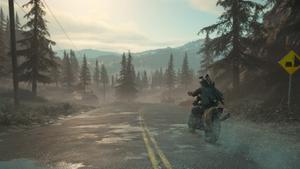 Deacon à moto allant vers l'horizon sur une route, avec une montagne au loin, après le passage de la pluie.