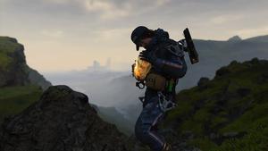 Sam tient son BB proche, sur une colline avec une ville au loin.