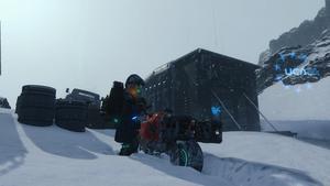 Sam à proxomité d'un refuge en haut d'une montagne enneigée.