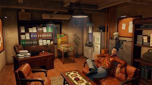 Vue d'ensemble du petit bureau de Yagami avec un bureau plein de paperasse et Kaito assis sur la canapé.