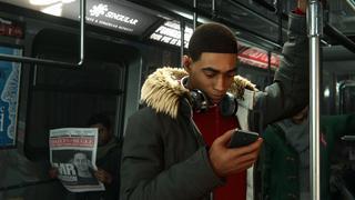 Miles, hors de son costume, se tient dans une rame de métro et regarde son téléphone.