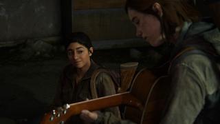 Ellie joue de la guitare de manière concentrée pendant que Dina la regarde attentivement avec un sourire.