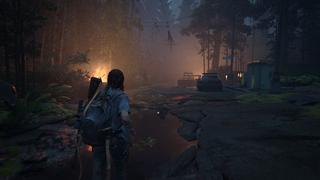 Ellie traverse une rue dévastée où des feux brûlent aux côtés de voitures détruites, et où la nature a repris ses droits.