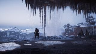 Plan large d'Eivor dans une grotte derrière une cascade, dans un environnement gêlé où de nombreuses stalactites sont visibles, avec des collines enneigées en arrière-plan.