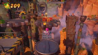Coco se tient sur une plateforme devant d'énormes engrenages à l'horizontale, avec des caisses normales, de TNT et de nitro le long du chemin, le tout dans une sorte de canyon plein de structures métalliques.