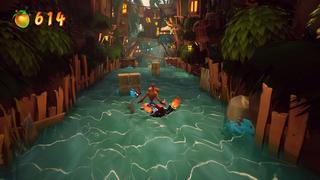 Crash navigue sa planche sur une petit rivière dans une jungle où il y a des maisons en hauteur, et des caisses devant lui.