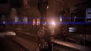 Shepard se tient sur une sorte de balcon qui donne sur une série de bâtiments très élevés et dont le côté futuriste se ressent par les angles et les matériaux des gratte-ciel.