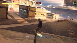 Tony Hawk effectue un grid Overcrook sur un rail le long d'un escalier avec un bâtiment de lycée en arrière plan.